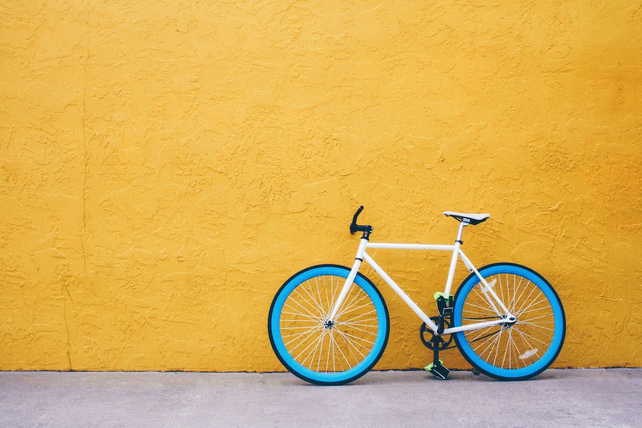 Blue bicycle against yellow wall