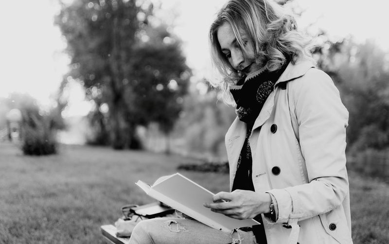 Monochrome Photography Young woman reading a book Tree Holding Focus On Foreground Leisure Activity Side View Young Adult Connection Casual Clothing Looking Down Person Hobbies Reading Relax Relaxation Relaxing Moments