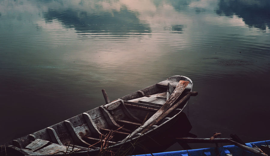 Man on boat moored in lake