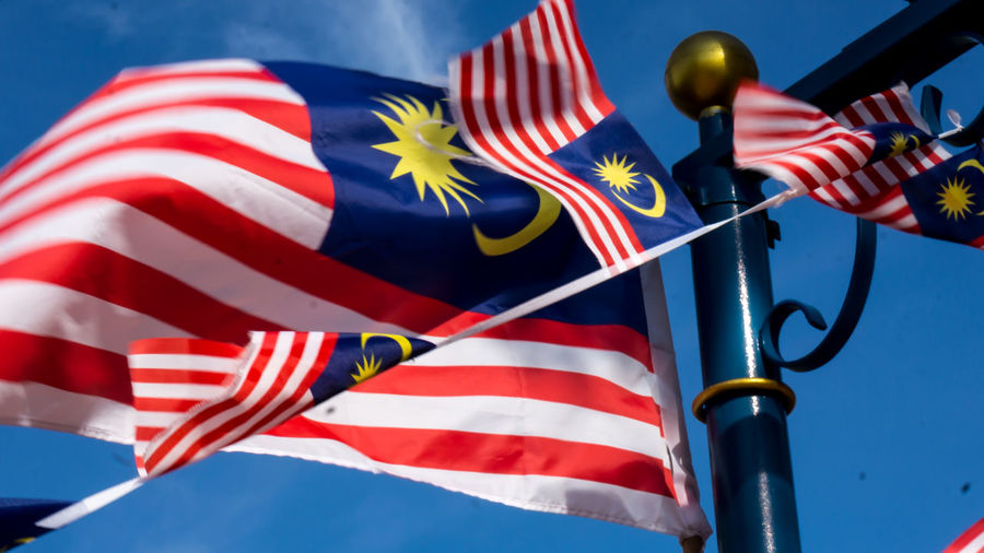 Waving Malaysian flag over the river in a sunny day (selective focus) ASIA Asian  Country Kuala Lumpur Kuala Lumpur Malaysia  National Patriotism Emblem  Flag Flags In The Wind  Independance Malaysia Malaysian