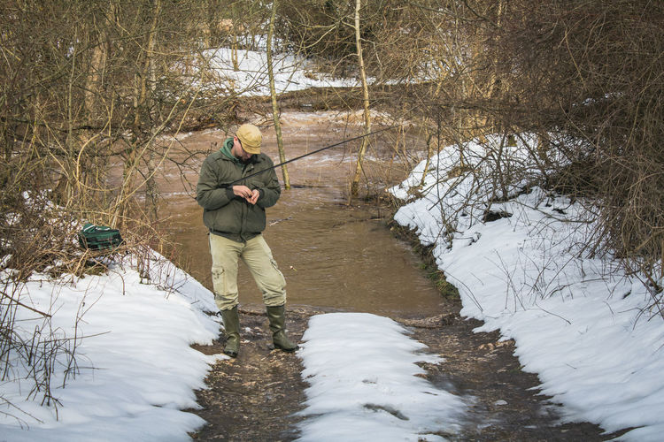 Man holding fishing pole while standing in forest during winter
