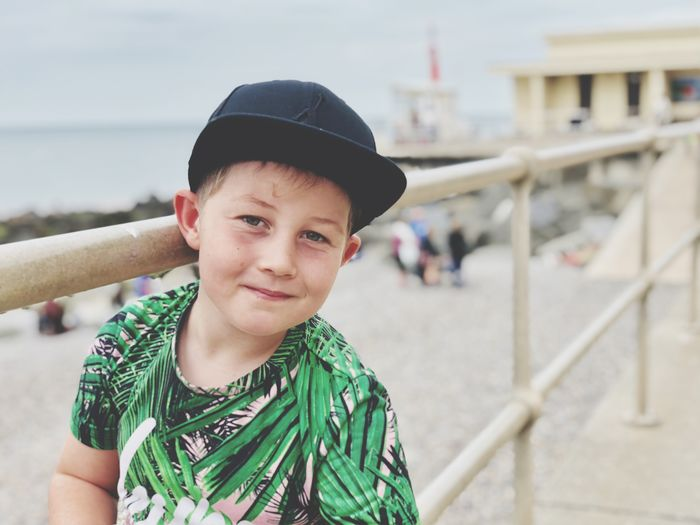Portrait of smiling boy standing by railing