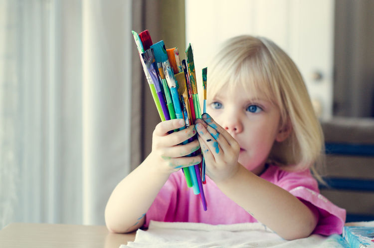 Young girl holding paintbrushes Activity Artist Arts And Crafts Blond Hair Child Childhood Children Only Close-up Copy Space Creativity Headshot Holding Home Interior Indoors  Innocence Kids Messy Multi Colored One Girl Only One Person Paint On Hands Paintbrushes Painting Portrait Young Girl