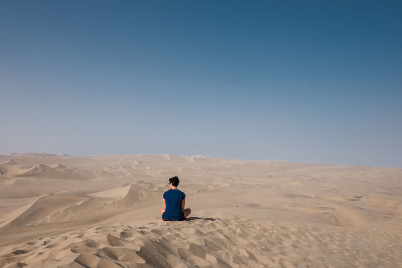 Rear view of man on sand dune in desert against clear sky