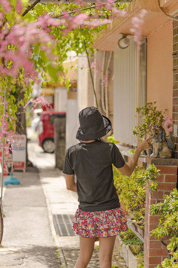 Girl from behind and shisa lion sculpture in naha city street in okinawa
