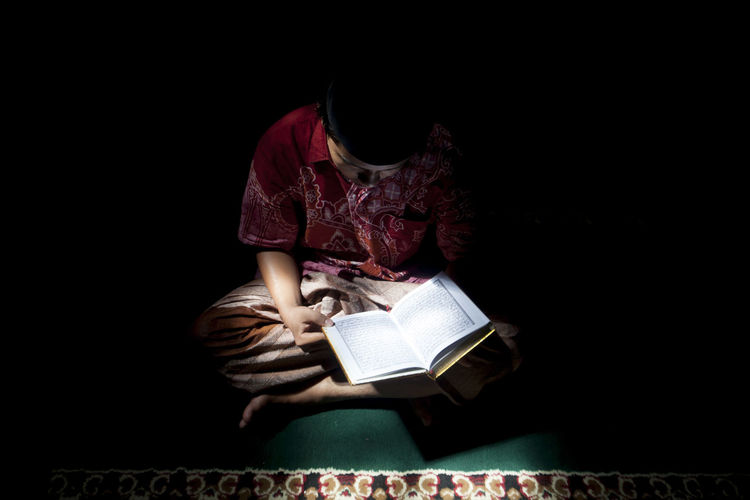 High angle view of boy reading koran in darkroom