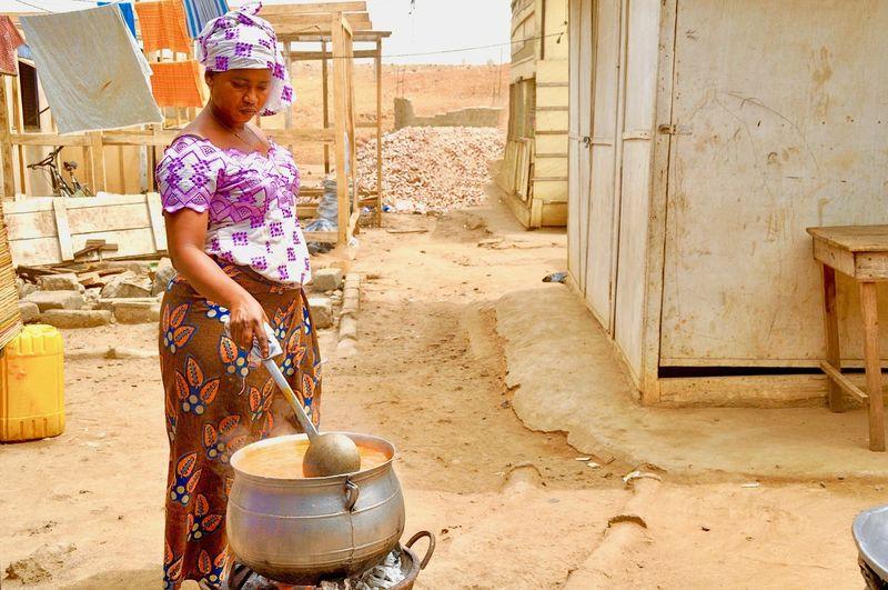 Woman preparing food on stove outside house