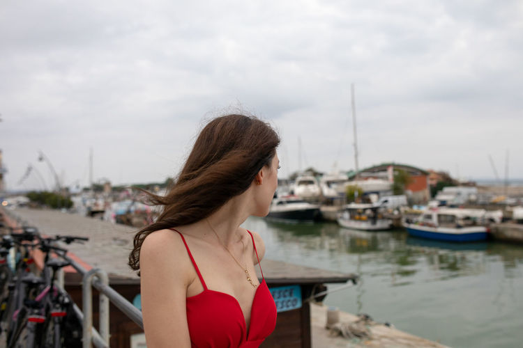 Woman looking at sailboat against sky
