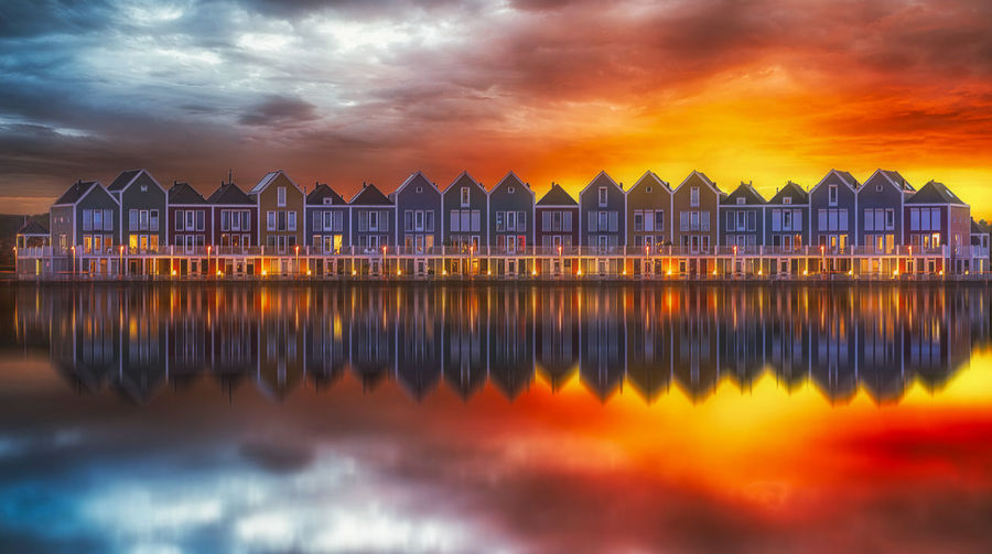 Reflection of buildings on sea against cloudy sky during sunset