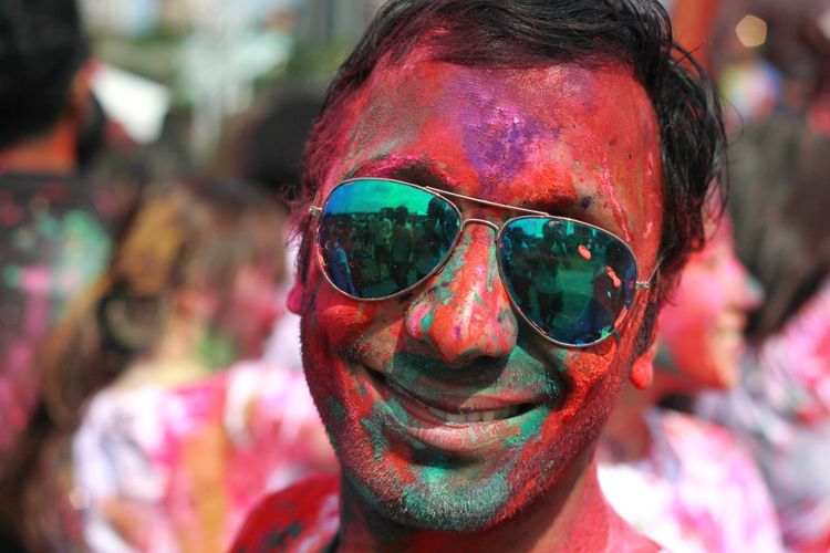 Portrait Of Smiling Man With Powder Paint On Face During Holi