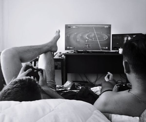 Rear view of friends playing video game at home