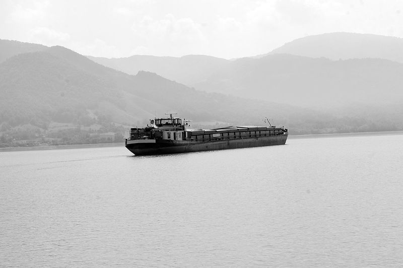 Barge sailing on danube river against mountains in foggy weather