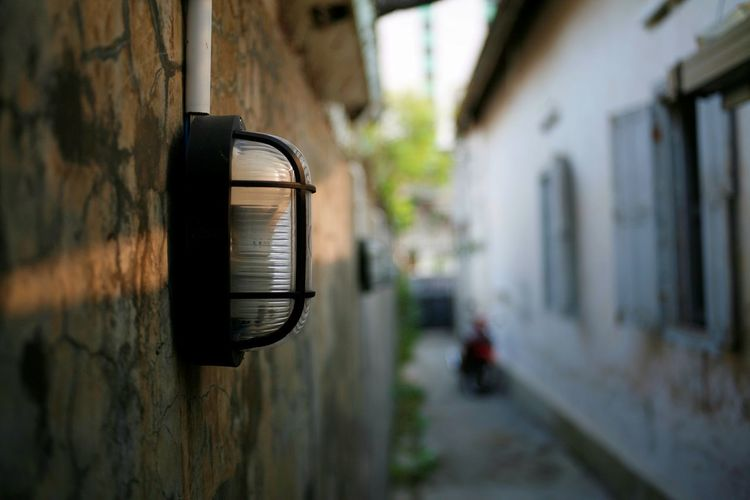 Close-up of electric lamp on wall by building