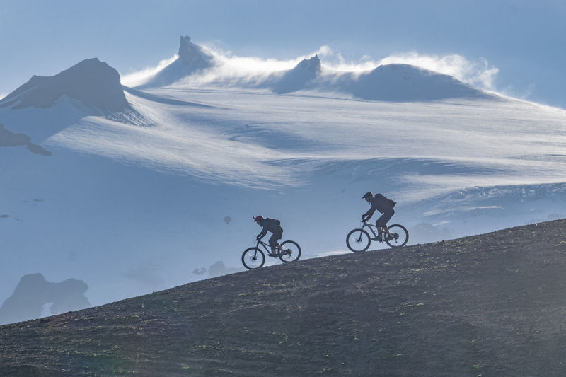 Men riding bicycle on mountain against sky