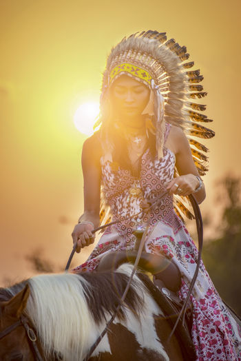Cowwoman riding horse at sunset