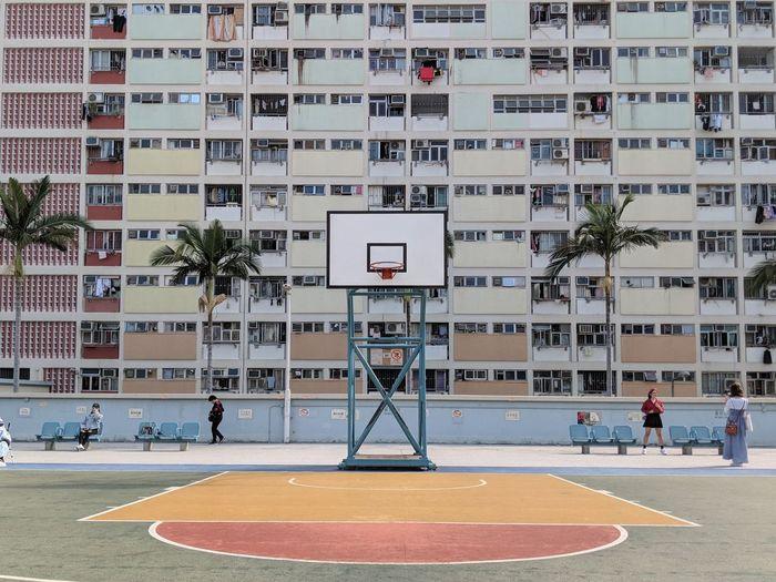 View of basketball hoop against buildings in city