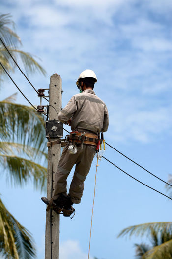 Rear view of man working on electricity pylon against sky