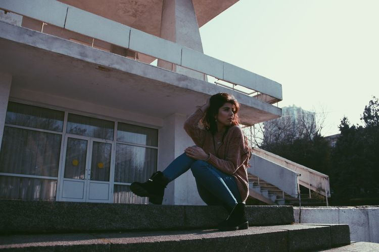 Portrait of woman sitting on railing against building