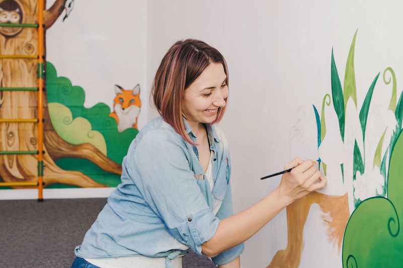 Woman painting wall at home