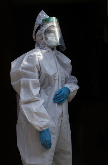 Portrait of woman wearing protective suit standing against black background