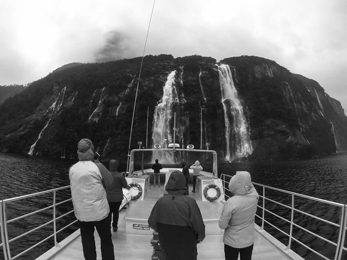 Rear View Of People Standing On Ship In Sea Against Waterfalls