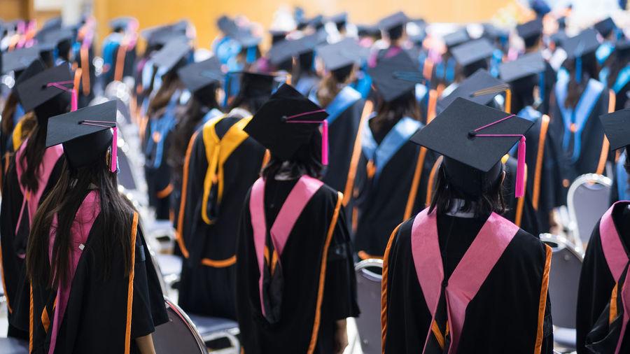 Women wearing graduation gown and mortarboard standing in university