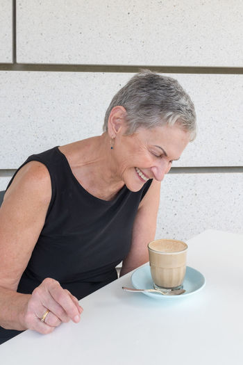 Senior women laughing Food And Drink One Person Coffee Cup Drink Coffee Cup Mug Coffee - Drink Refreshment Adult Front View Real People Table Smiling Waist Up Women Leisure Activity Holding Mature Adult Hot Drink Drinking Crockery Glass Senior Women