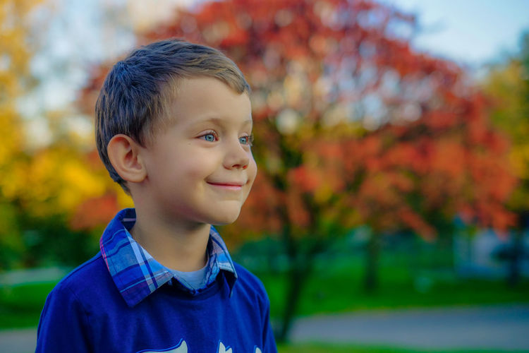 Close-up of smiling boy looking away
