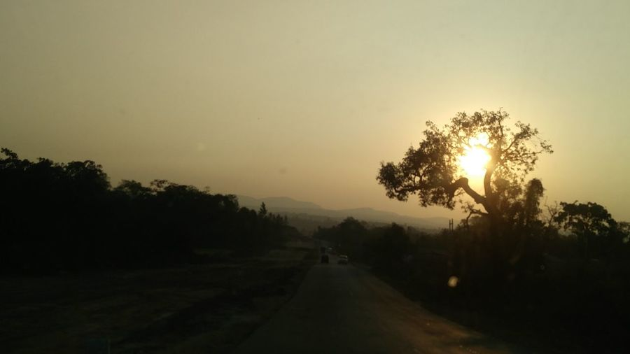 From Plains to hills... Through the windscreen, a drive-by shot of setting sun. An Eye For Travel Shades Of Winter Sunday Morning Road Side View Drivingshots Western Ghats India Naturephotography Take A Break Sunset_collection Through The Window Through The Trees Evening Sun Mountain View Winding Road Tree Fog Sunset Morning Outdoors Nature No People