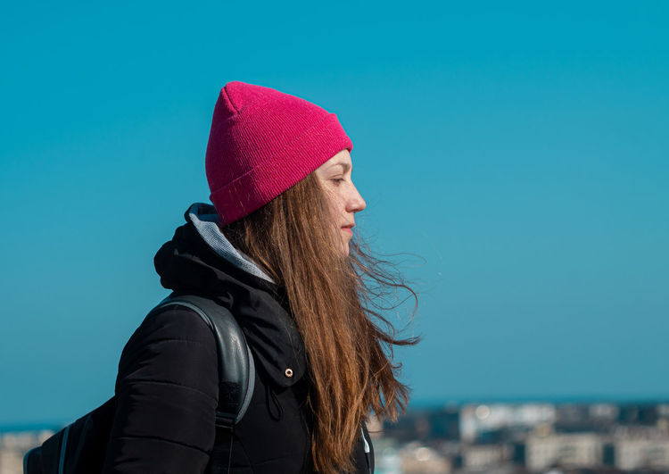 Young confident woman long hair in pink hat black coat. stylish millennial girl walks sky background