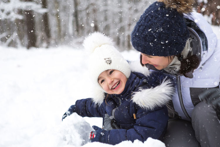 Mother and daughter in snow during winter