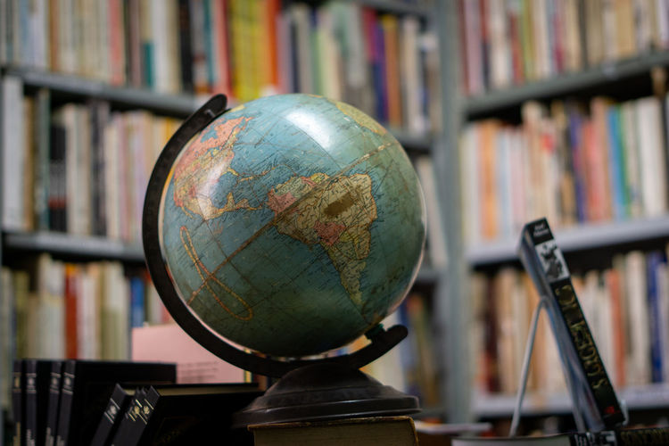 Close-up of globe against bookshelf at library