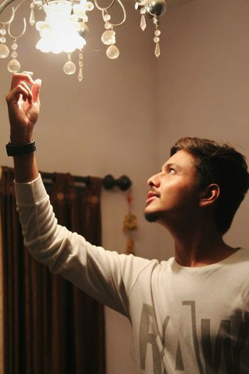 Young man touching chandelier at home