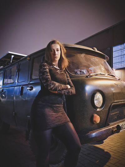 Portrait of woman leaning on van