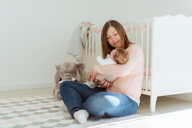 Young woman with cat sitting at home