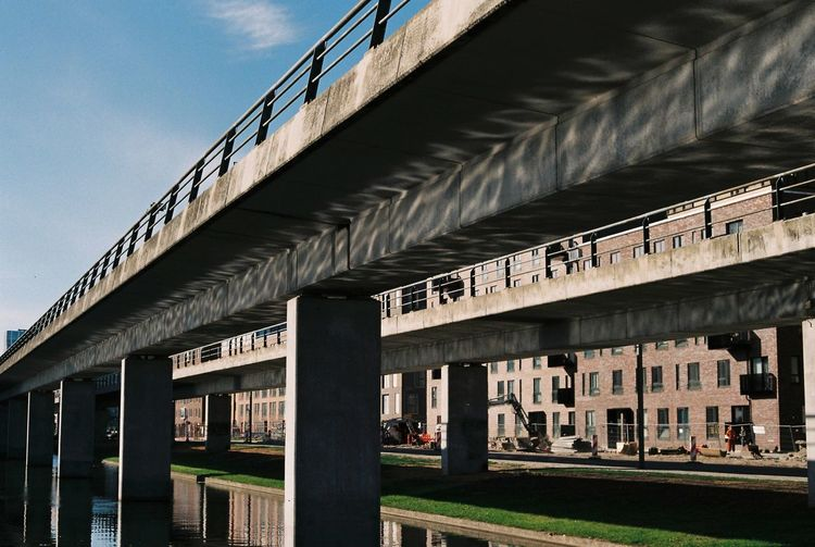Low angle view of bridge against buildings and sky in city