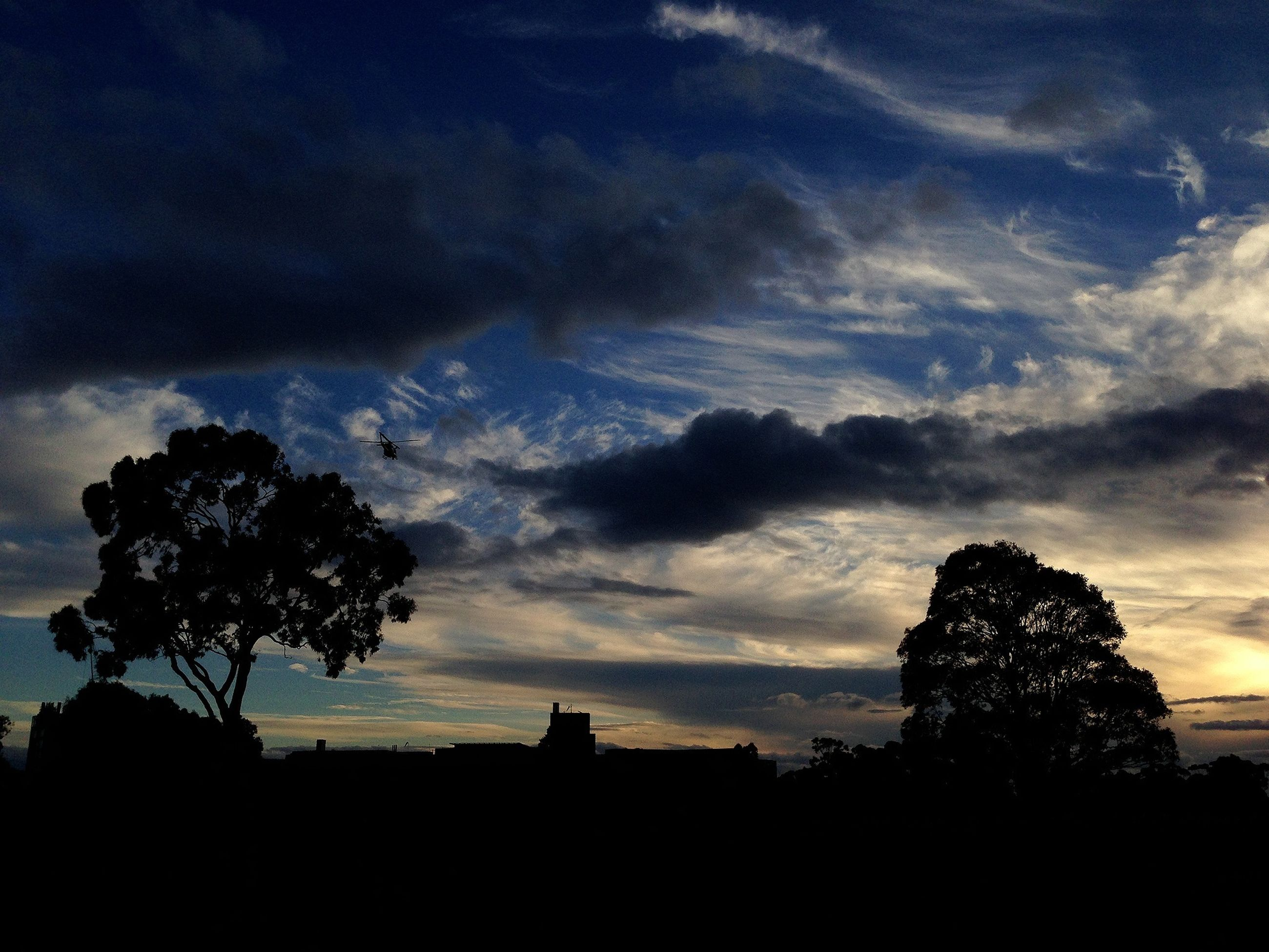 silhouette, sky, cloud - sky, tree, sunset, low angle view, cloudy, built structure, cloud, beauty in nature, nature, scenics, dusk, tranquility, building exterior, architecture, tranquil scene, dramatic sky, dark, outline