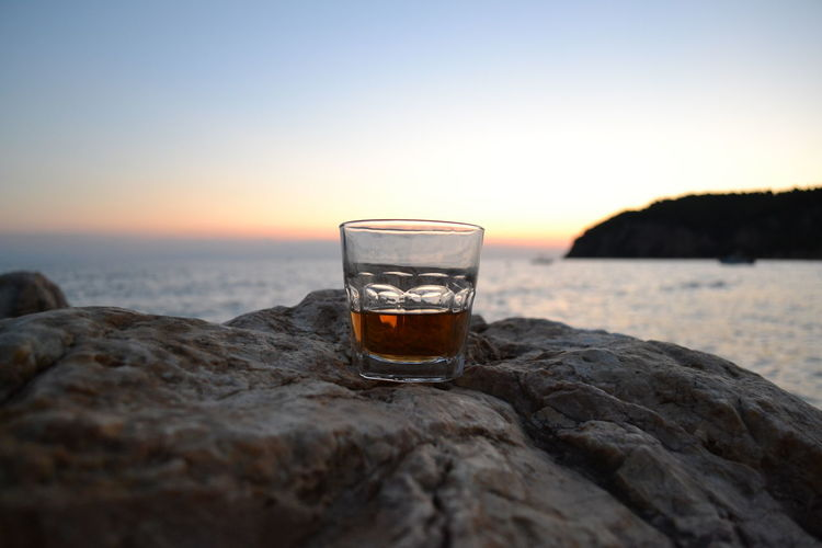 Whiskey Glass On Rock Against Sea During Sunset