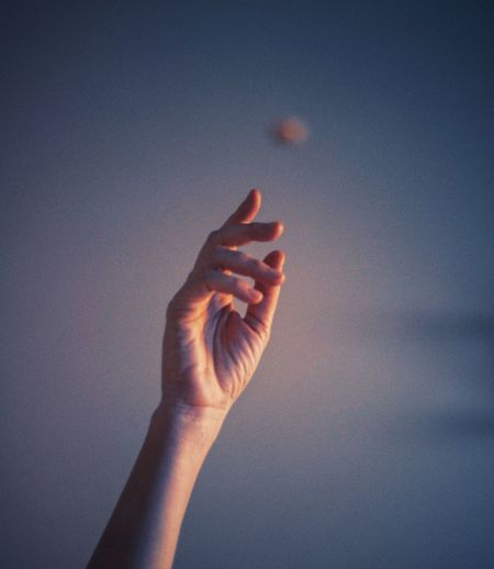 Low angle view of hand against sky during sunset