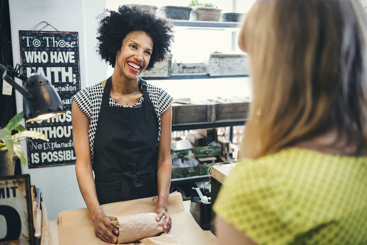 Smiling young woman standing at store