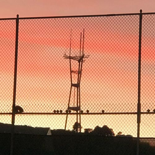 Silhouette chainlink fence against sky during sunset