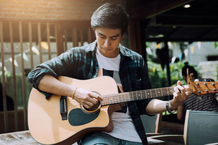 Young man playing guitar while sitting on table at outdoor restaurant