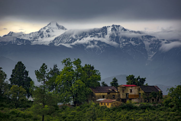 Houses on snowcapped mountains against sky