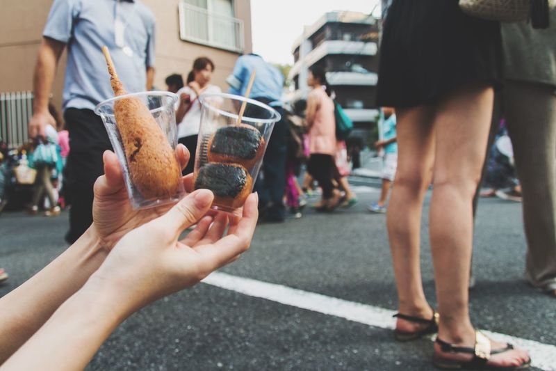 Close-Up Of Cropped Woman Hand Holding Japanese Food On Street Against Buildings