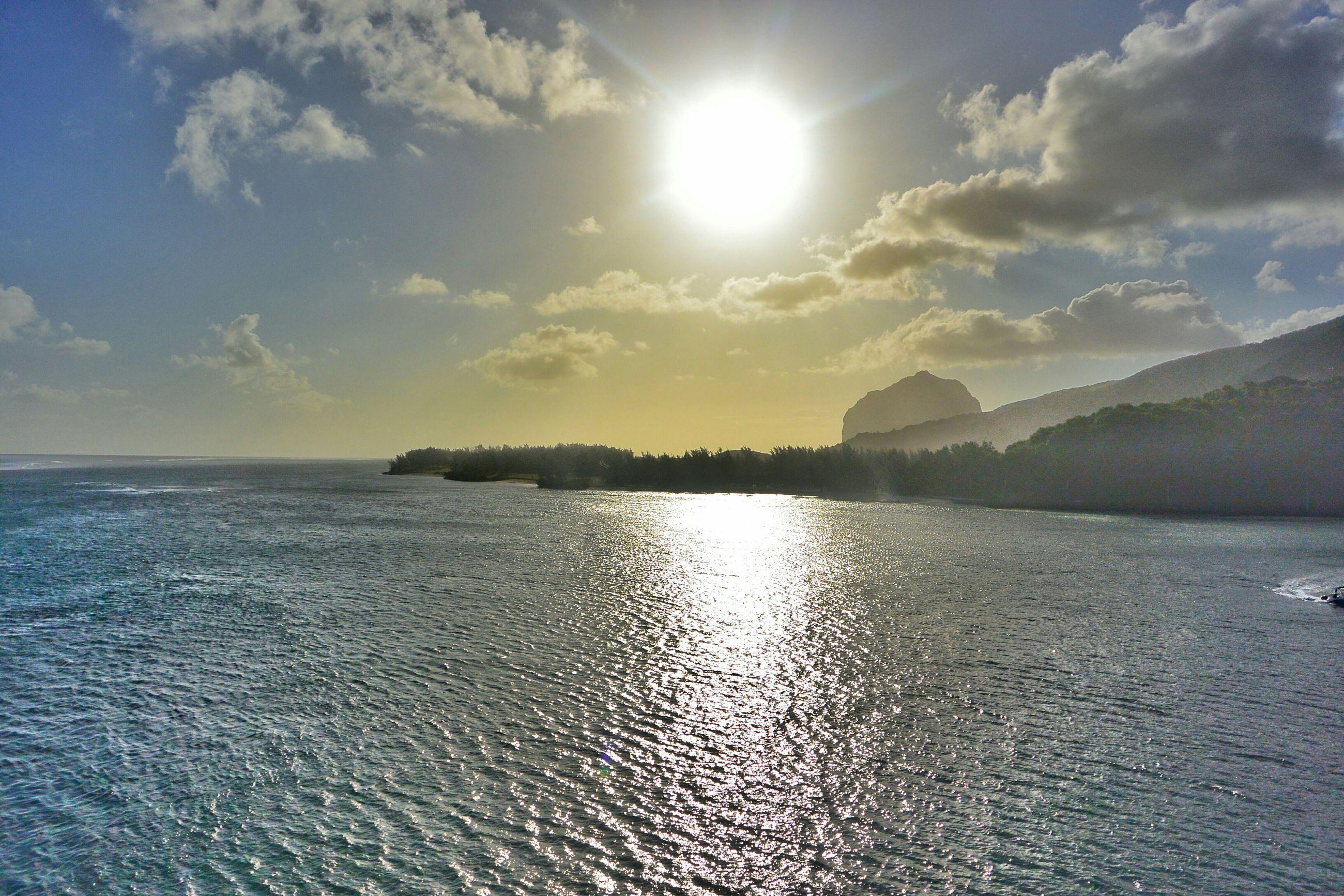 water, sun, tranquil scene, tranquility, scenics, reflection, sky, beauty in nature, sunlight, sea, sunbeam, nature, waterfront, mountain, rippled, idyllic, lens flare, lake, cloud - sky, sunset