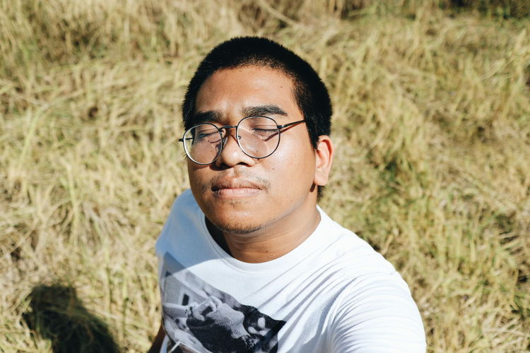 Portrait of young man wearing eyeglasses on field