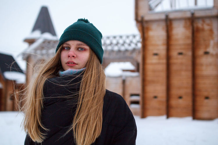Portrait of young woman with long hair standing outdoors during winter