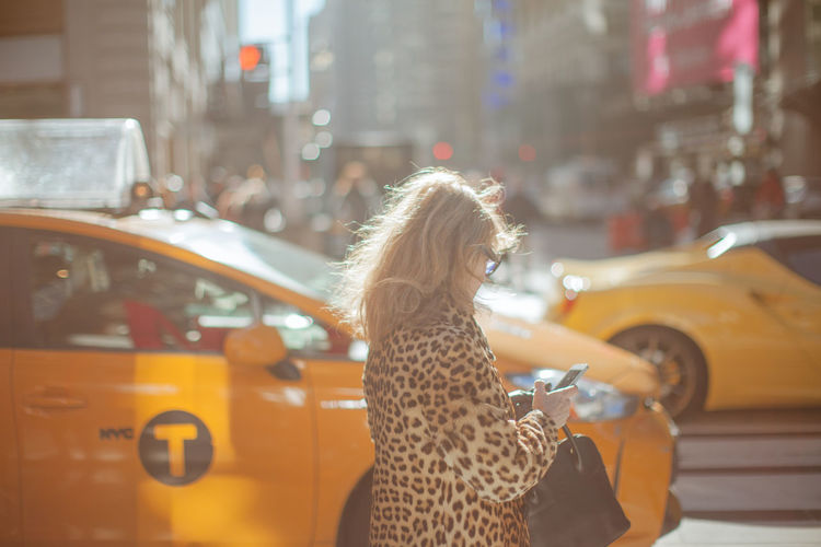 Side view of woman in cheetah print cloth walking on street