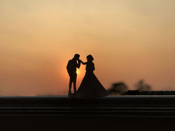 Silhouette man kissing on woman hand against sky during sunset