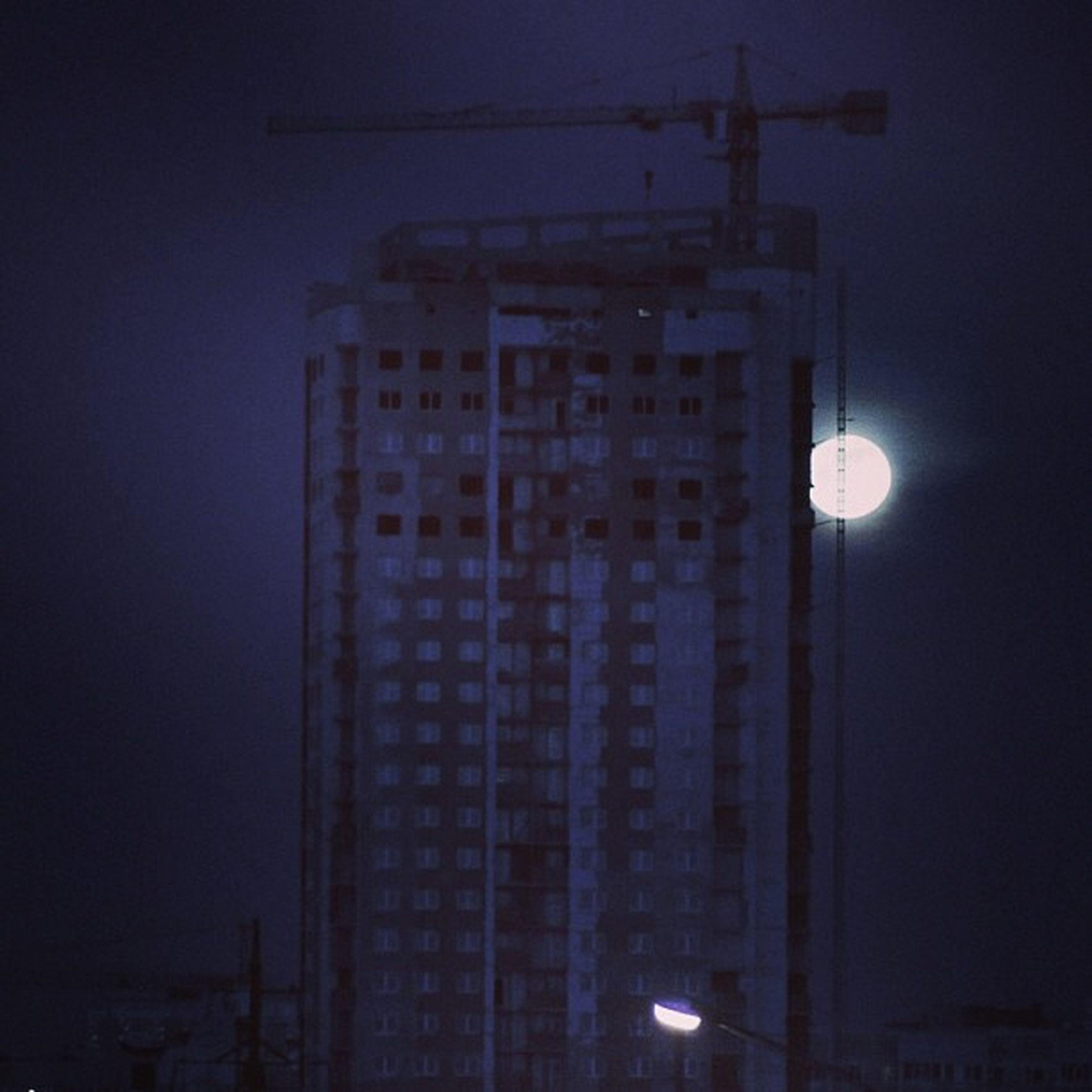 building exterior, architecture, built structure, low angle view, night, illuminated, electricity, street light, city, sky, building, lighting equipment, development, clear sky, crane - construction machinery, dusk, tall - high, tower, fuel and power generation, outdoors